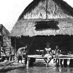 verandaHE VERANDA AT HIGH TIDE: The houses are built upon high piles, and at low tide stand some ten to twelve feet above water level. But at high tide, the lagoon deepens and the veranda becomes a convenient land platform for the canoes which are the only means of transportation in this water Venice.
